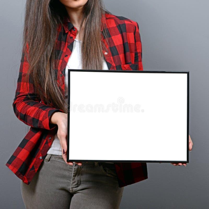 Portret uśmiechnięta kobiety mienia pustego miejsca znaka deska Pracowniany portret młoda kobieta z znak kartą przeciw szaremu tł zdjęcia stock