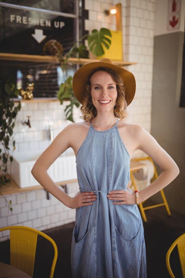 Portret uśmiechnięta kobiety pozycja z rękami na biodrze przy sklep z kawą obraz royalty free