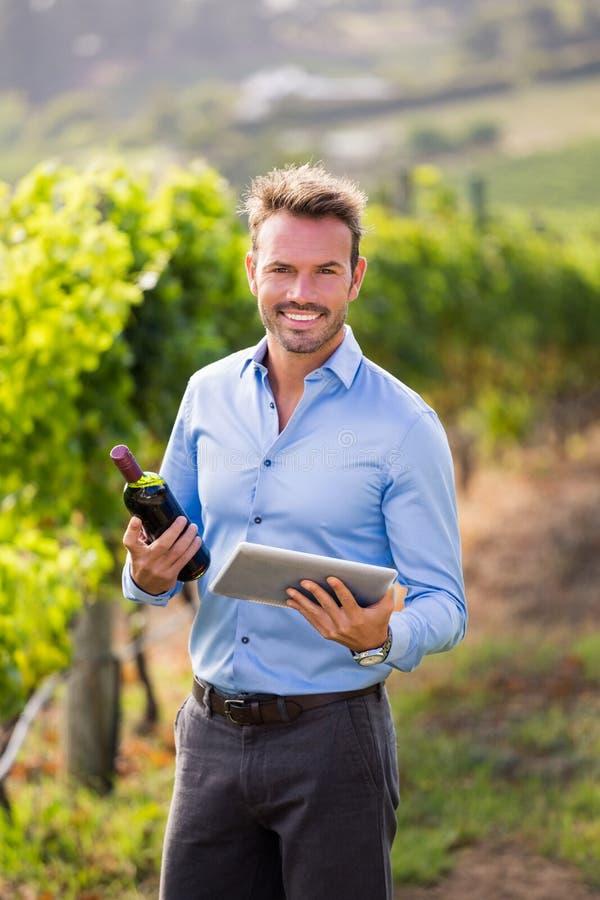 Portret uśmiechnięta mężczyzna mienia wina butelka i pastylka obrazy royalty free
