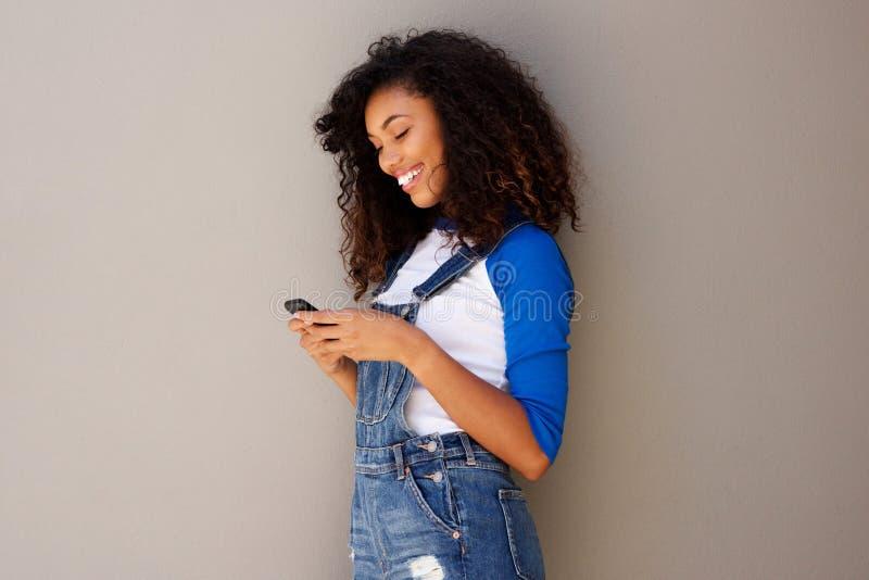 Portret uśmiechnięta młoda amerykanin afrykańskiego pochodzenia kobieta patrzeje telefon komórkowego zdjęcia stock