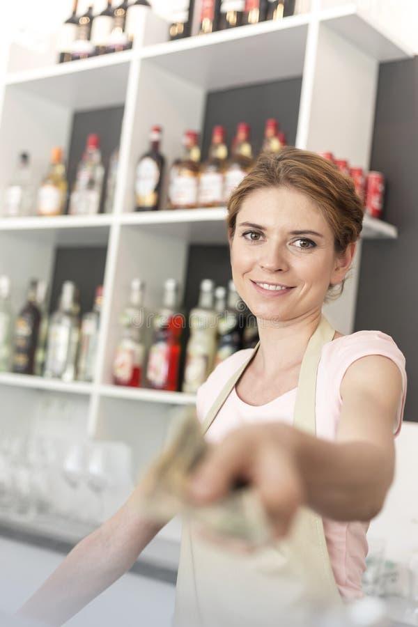 Portret uśmiechnięta młoda kelnerka daje pieniądze podczas gdy stojący przy kontuarem w restauracji obrazy royalty free