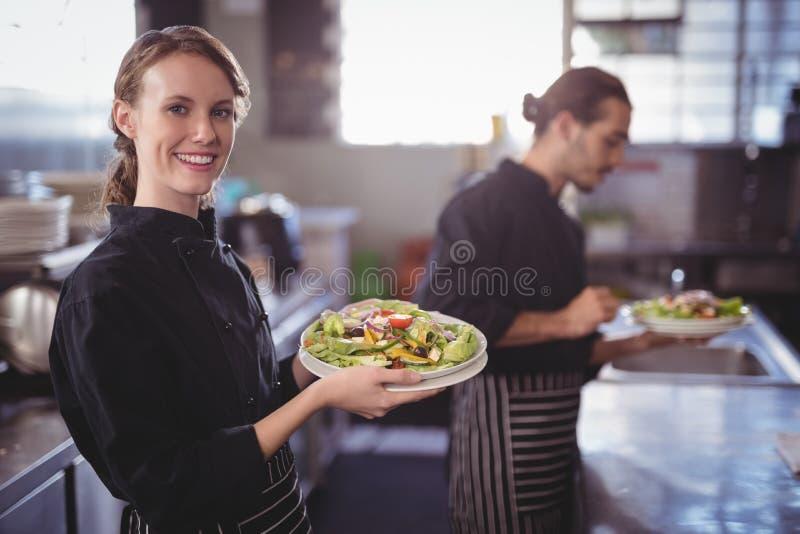 Portret uśmiechnięta młoda kelnerka trzyma świeżej sałatki przeciw kelnerowi przy handlową kuchnią obrazy royalty free