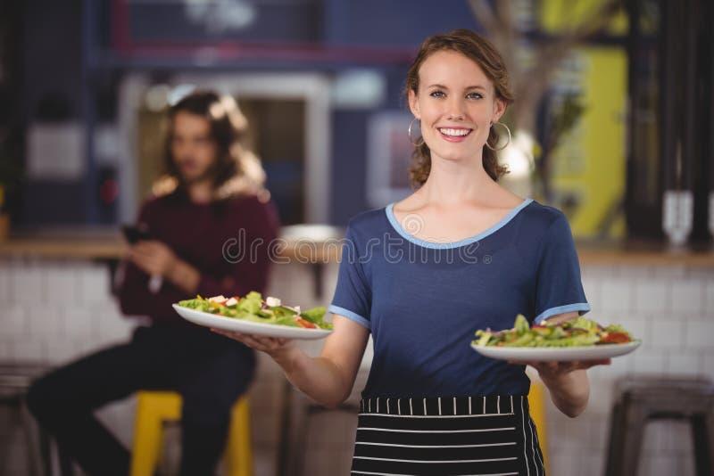 Portret uśmiechnięta młoda kelnerki pozycja z świeżymi sałatkowymi talerzami obraz royalty free