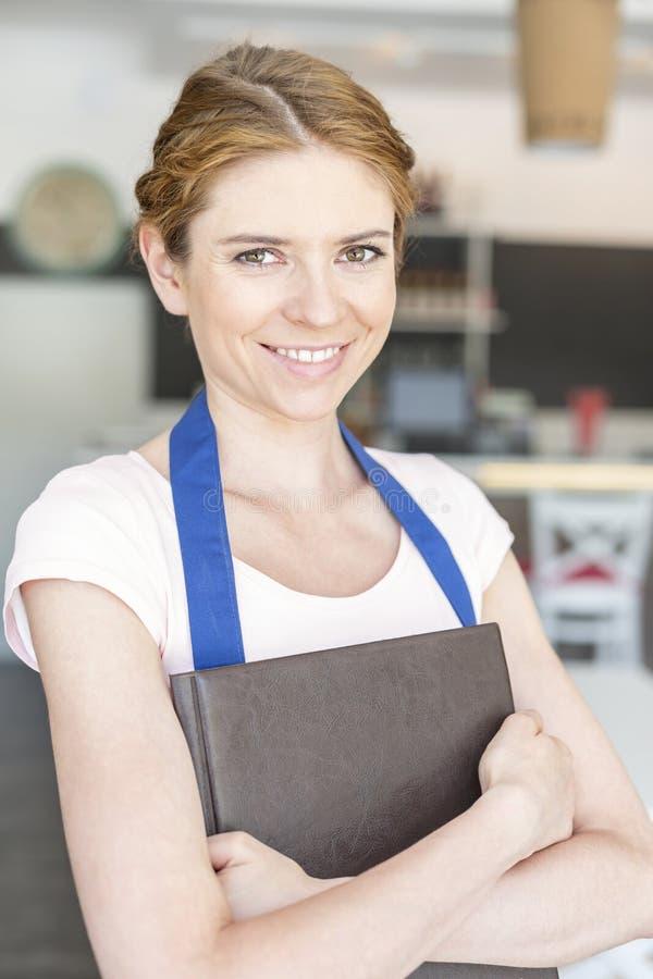 Portret uśmiechnięta młoda kelnerki pozycja z mienie menu przy restauracją fotografia stock