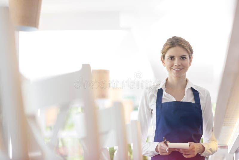 Portret uśmiechnięta młoda kelnerki pozycja z notepad w restauracji obrazy royalty free