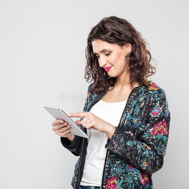 Portret uśmiechnięta młoda kobieta używa cyfrową pastylkę zdjęcia royalty free