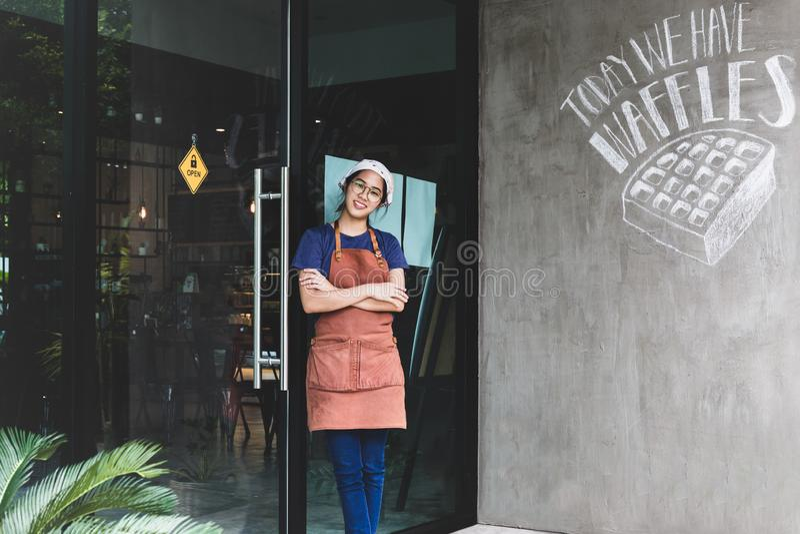 Portret uśmiechnięta młoda kobieta z rękami krzyżował pozycję przy sklep z kawą zdjęcia royalty free