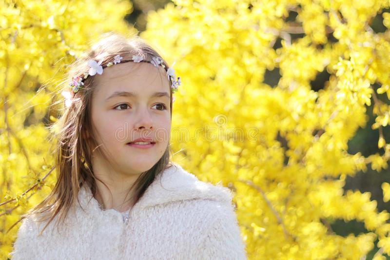 Portret uśmiechnięta mała dziewczynka z handmade włosianym wiankiem na żółtych forsycjach kwitnie tło obrazy stock