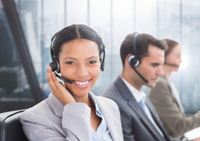 Portret uśmiechnięta obsługi klienta kobieta opowiada na słuchawki obrazy stock