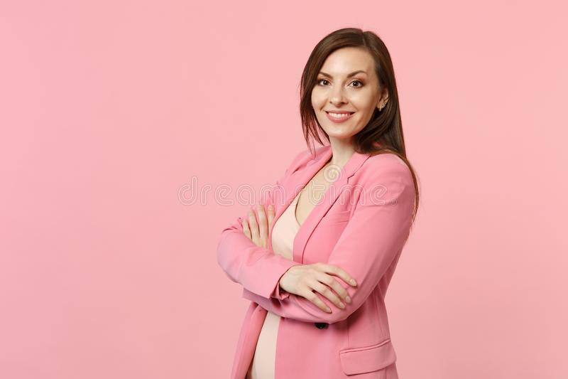 Portret uśmiechnięta oszałamiająco młoda kobieta w kurtki pozycji, mienie wręcza krzyżujący odosobnionego na pastelowych menchii  zdjęcie stock