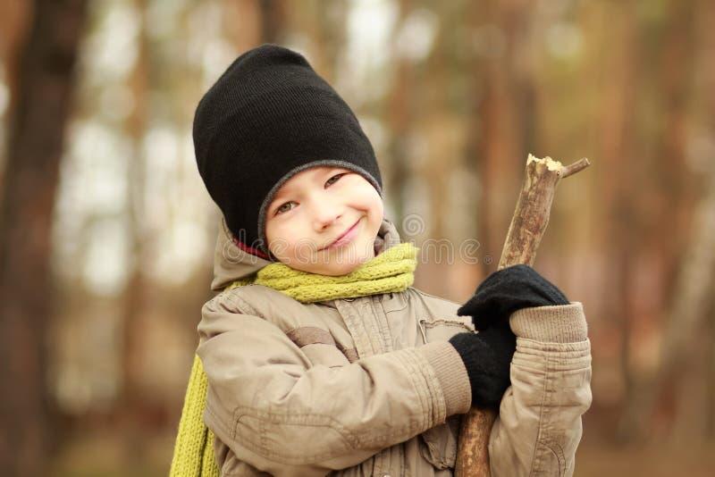 Portret uśmiechnięta pięcioletnia stara chłopiec w kapeluszu i szaliku w jesieni parkowy bawić się z kija pistoletem zamazujący t obrazy stock