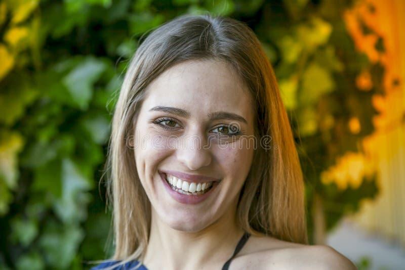 Portret uśmiechnięta piękna dziewczyna przed zielenią zdjęcie stock