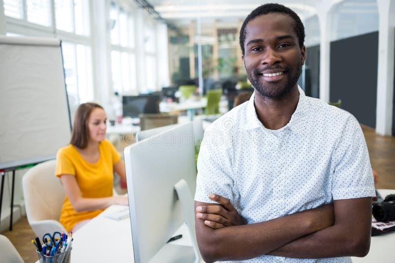 Portret uśmiechnięta projektant grafik komputerowych pozycja z rękami krzyżować obraz stock