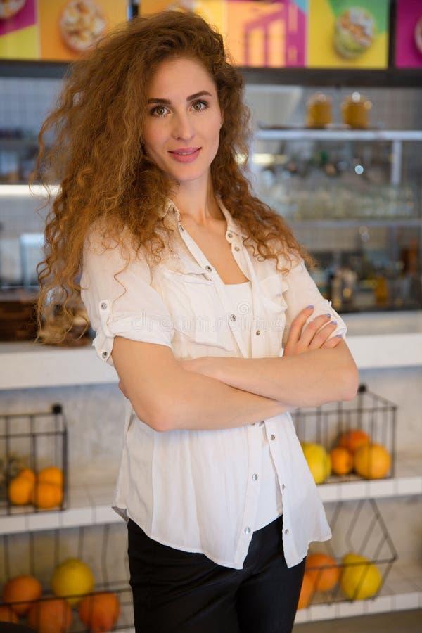 Portret uśmiechnięta rudzielec kelnerki pozycja z rękami krzyżować obraz royalty free