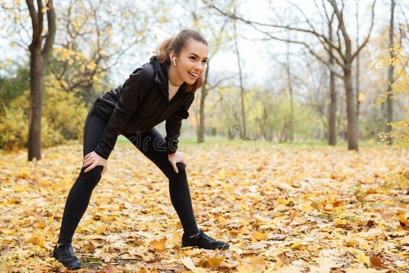 Portret uśmiechnięta sprawności fizycznej dziewczyna w słuchawek odpoczywać zdjęcie stock