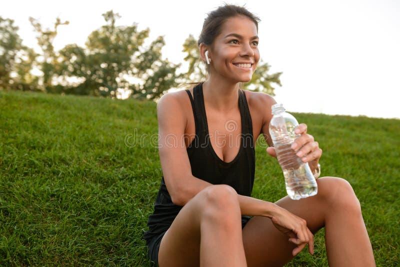 Portret uśmiechnięta sprawności fizycznej kobieta w słuchawek odpoczywać fotografia royalty free