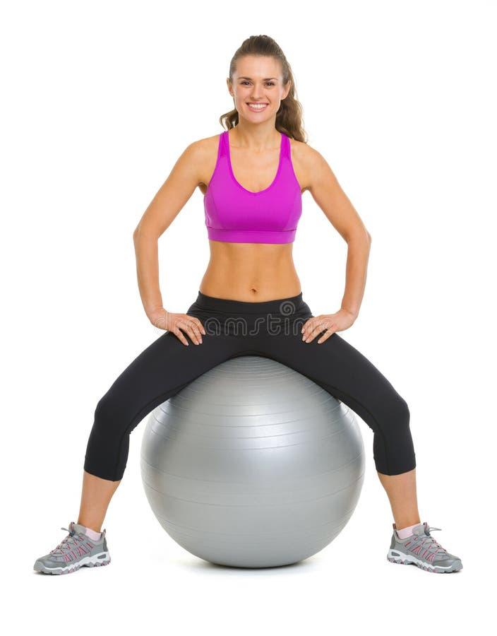 Portret uśmiechnięta sprawności fizycznej młoda kobieta na sprawności fizycznej piłce fotografia stock