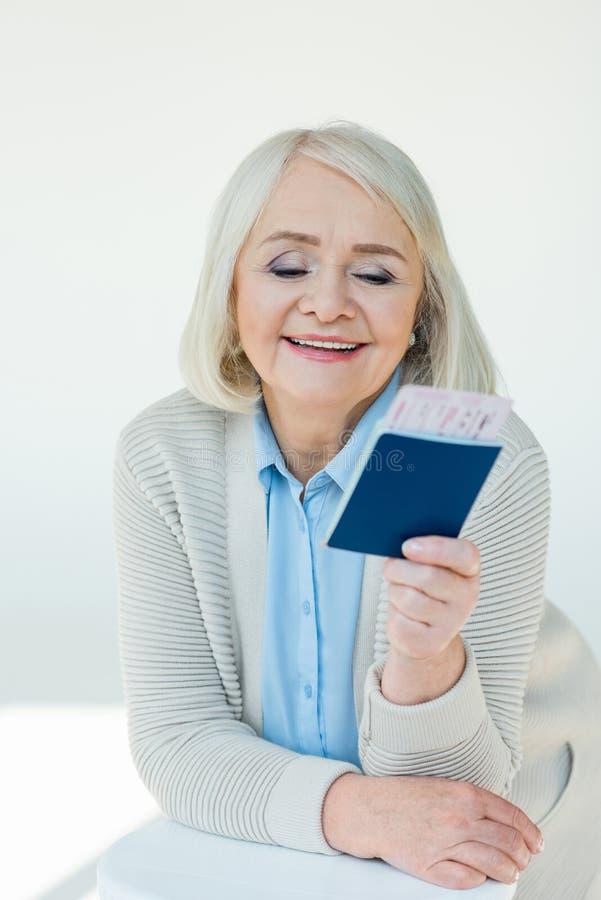 Portret uśmiechnięta starsza kobieta patrzeje paszporty i bilety zdjęcie royalty free