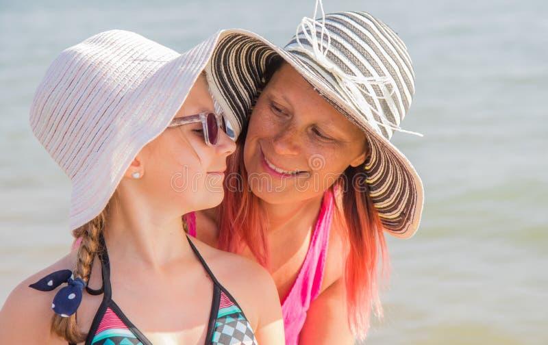 Portret uśmiechnięta szczęśliwa matka i mała córka śmia się wpólnie na pogodnej plaży obraz royalty free