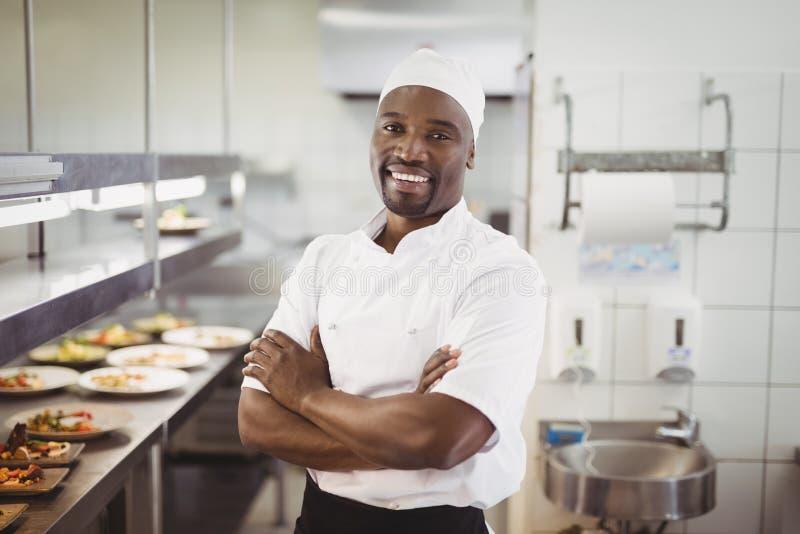 Portret uśmiechnięta szef kuchni pozycja z rękami krzyżował w handlowej kuchni zdjęcia stock