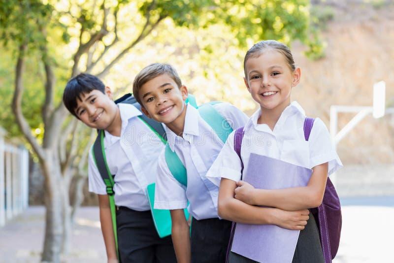 Portret uśmiechnięta szkoła żartuje pozycję w kampusie fotografia stock