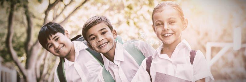Portret uśmiechnięta szkoła żartuje pozycję w kampusie fotografia royalty free