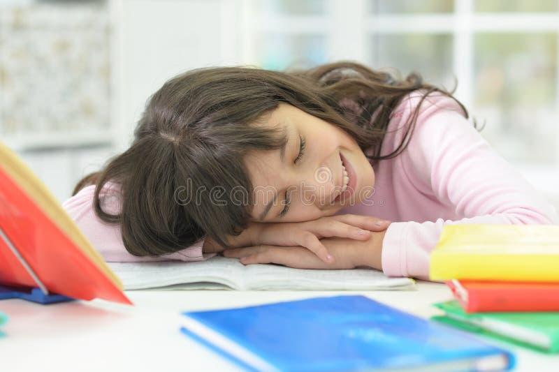 Portret uśmiechnięta uczennica odpoczywa przy biurkiem po studiować zdjęcie stock