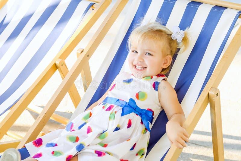 Portret uśmiechnięta urocza blondy dziewczynka w dziecku relaksuje na sunbed, deckchair w miasto parka recre lub obraz stock