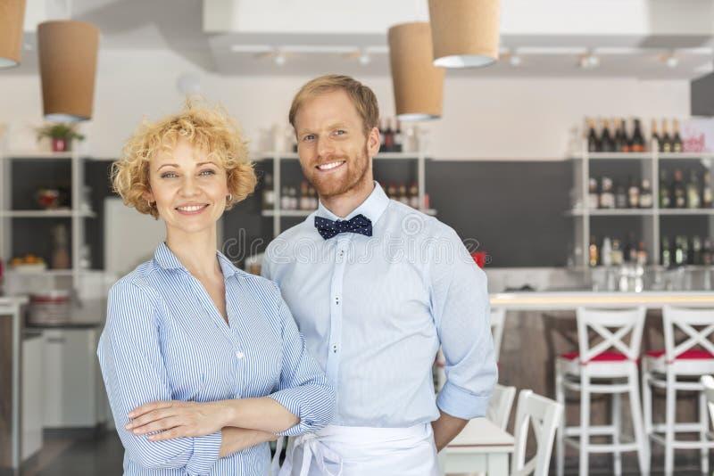 Portret uśmiechnięta właściciela i kelnera pozycja przeciw meble przy restauracją zdjęcie stock
