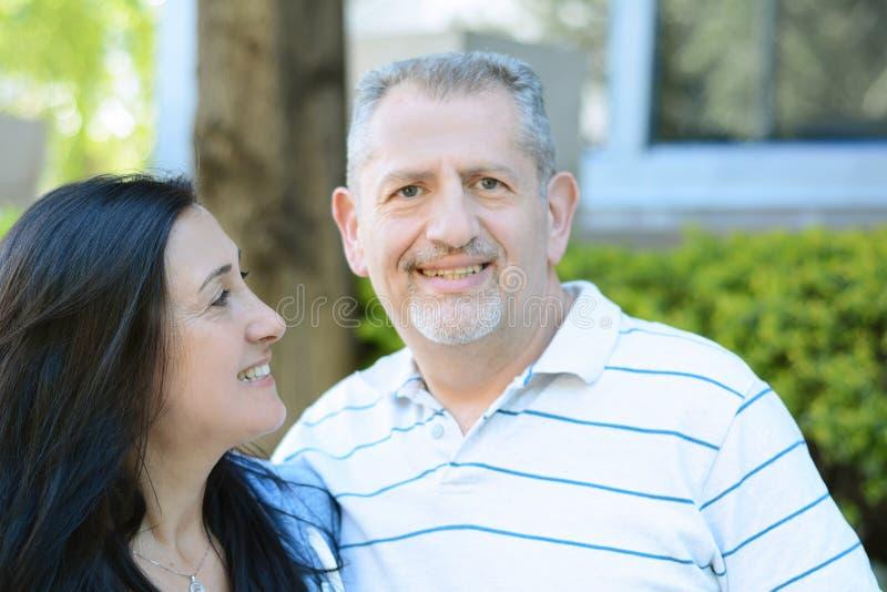 Portret uśmiechnięta w średnim wieku para patrzeje naprzód fotografia stock