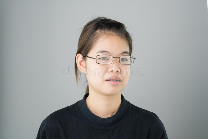 Portret uśmiechnięte azjatykcie młode kobiety stawia dalej brasy na szarości tło daje miękkiemu światłu obraz stock
