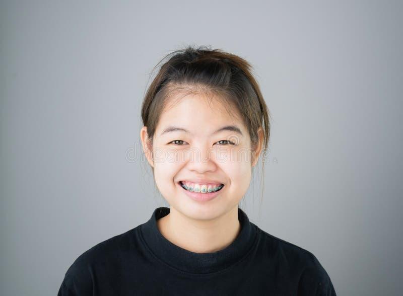 Portret uśmiechnięte azjatykcie młode kobiety stawia dalej brasy na szarości tło daje miękkiemu światłu fotografia stock