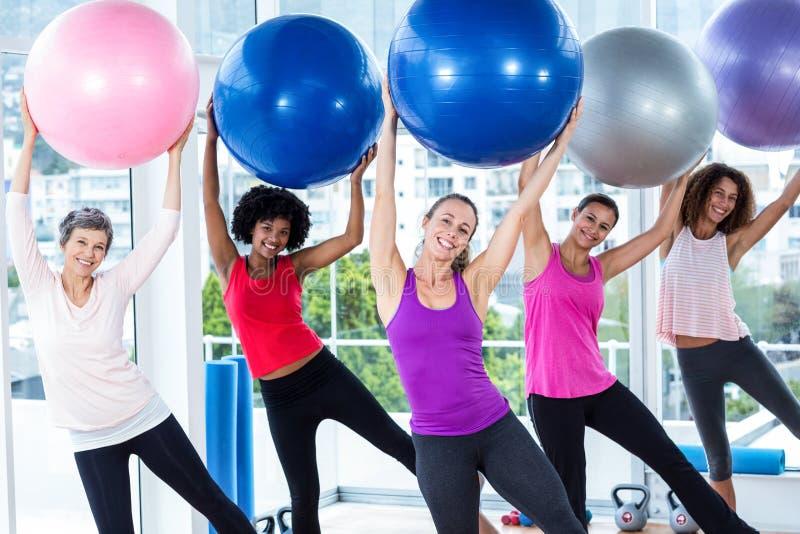 Portret uśmiechnięte kobiety trzyma ćwiczenie piłki podnosić z rękami fotografia stock