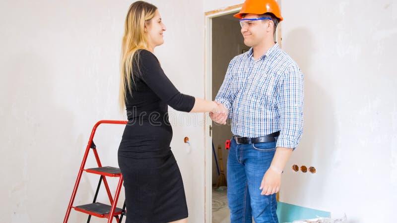 Portret uśmiechnięte młode bizneswomanu chwiania ręki z męskim pracownikiem budowlanym obraz stock