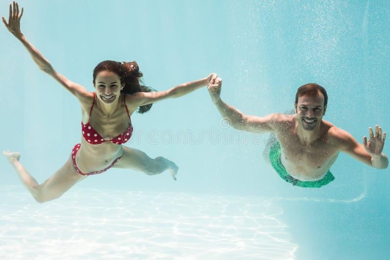 Portret uśmiechnięte pary mienia ręki podczas gdy pływający zdjęcia stock