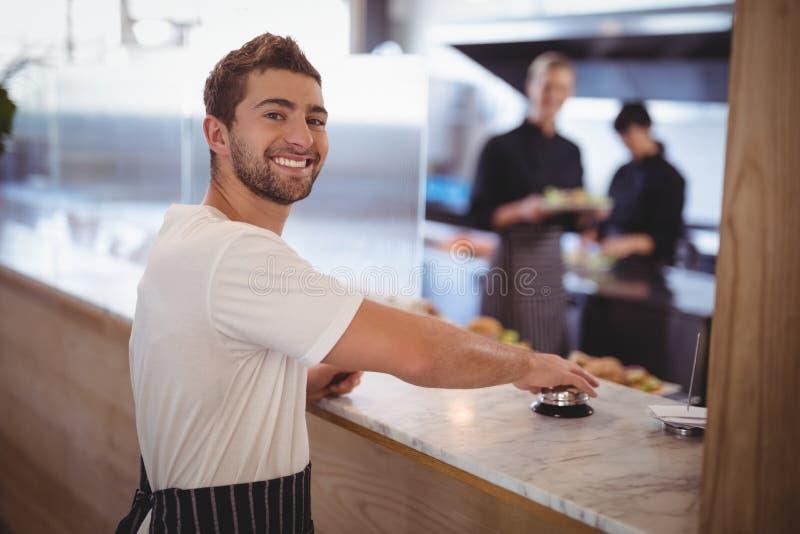 Portret uśmiechniętego kelnera naciskowy dzwon na kontuarze fotografia royalty free