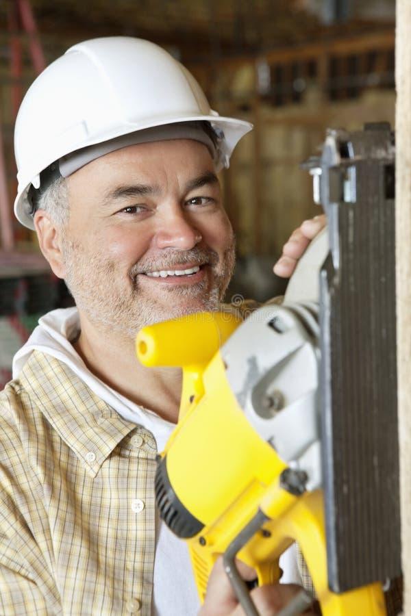 Portret uśmiechniętego męskiego pracownika budowlanego tnący drewno z kółkowym saw obraz stock