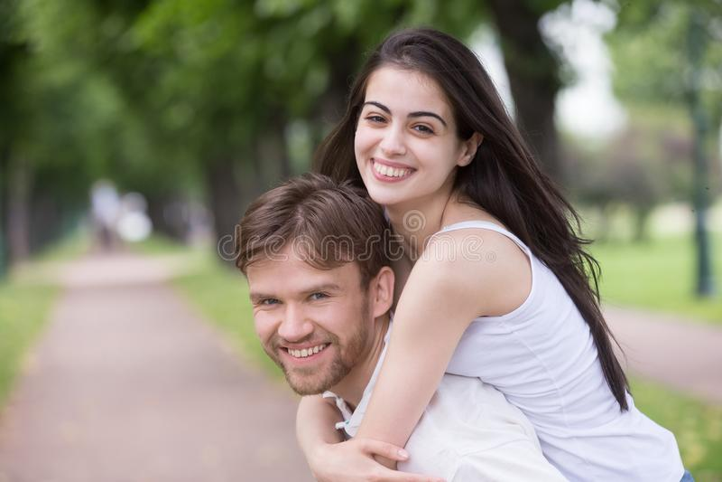 Portret uśmiechniętego młodego dziewczyny piggyback millennial boyfri obrazy royalty free