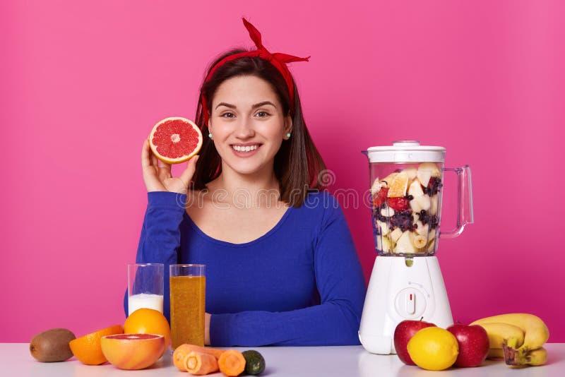 Portret uśmiechniętego pozytywnego żeńskiego mienia rżnięta owoc w jej ręce Potomstwo model czekać na smoothie być gotowy Rozocho zdjęcie stock