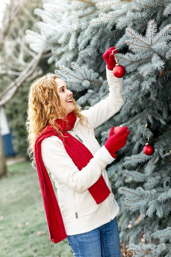 Kobieta dekoruje choinki outside obrazy royalty free
