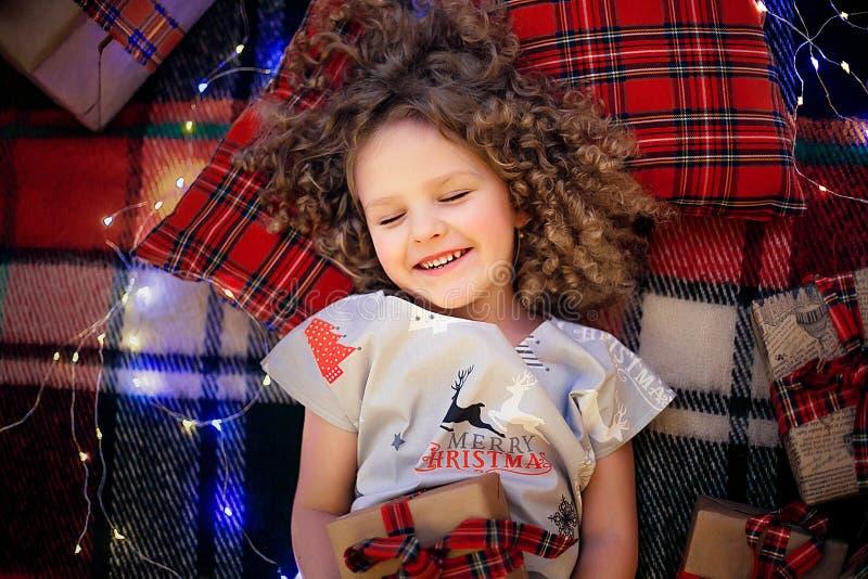 Portret uśmiechnięty śliczny małe dziecko trzyma prezenta pudełko w wakacyjnych boże narodzenie piżamach Odgórny widok obrazy royalty free