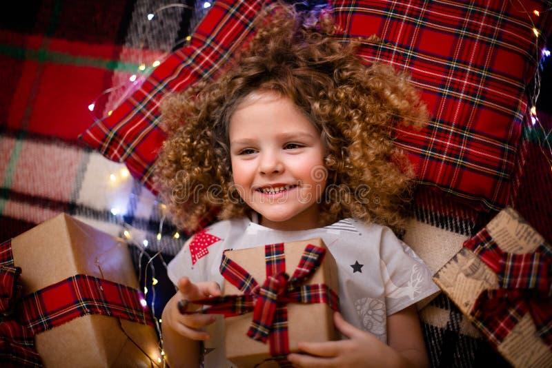 Portret uśmiechnięty śliczny małe dziecko trzyma prezenta pudełko w wakacyjnych boże narodzenie piżamach Odgórny widok obraz royalty free