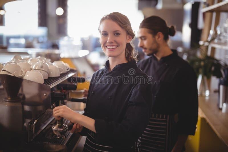 Portret uśmiechnięty żeński barista używać kawa espresso producenta przeciw kelnerowi fotografia stock