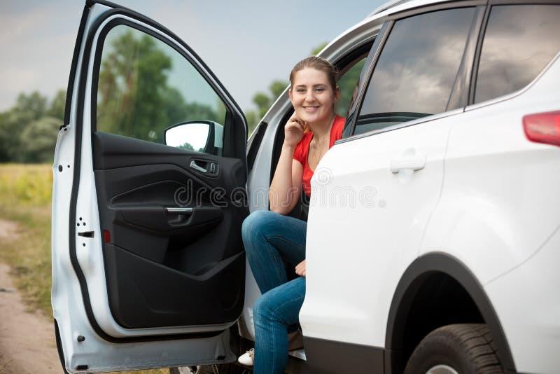 Portret uśmiechnięty żeński kierowca relaksuje w samochodzie przy polem fotografia royalty free