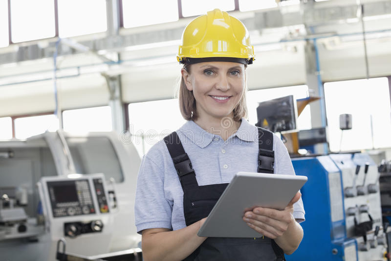 Portret uśmiechnięty żeński pracownik używa cyfrową pastylkę w przemysle wytwórczym fotografia stock