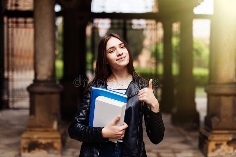 Portret uśmiechnięty żeński uczeń pokazuje kciuk w górę outdoors w kampusie zdjęcie royalty free