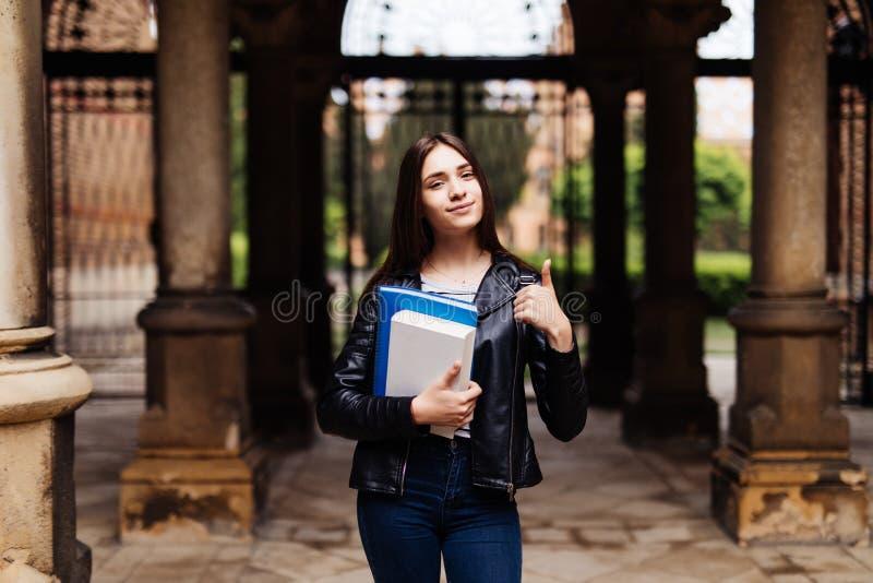 Portret uśmiechnięty żeński uczeń pokazuje kciuk w górę outdoors w kampusie fotografia royalty free