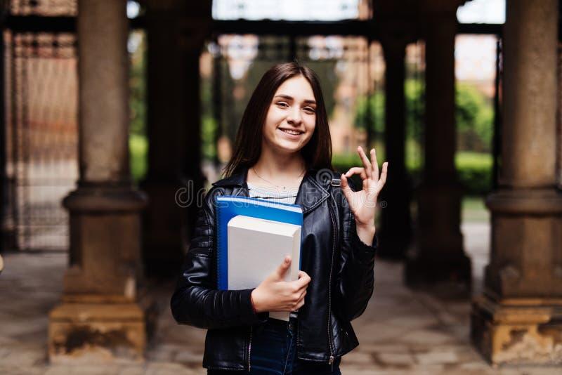 Portret uśmiechnięty żeńskiego ucznia seansu ok znak outdoors w kampusie zdjęcia stock