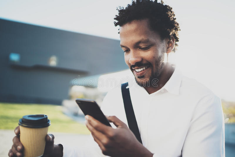 Portret Uśmiechnięty Amerykański Afrykański mężczyzna w hełmofonie przy pogodnym miastem z kawą wewnątrz bierze oddaloną filiżank zdjęcie royalty free