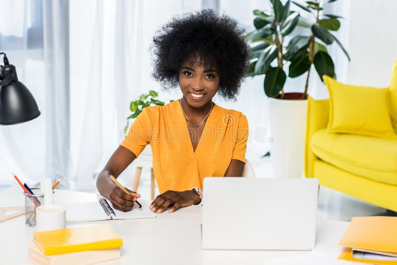 portret uśmiechnięty amerykanin afrykańskiego pochodzenia freelancer przy miejsce pracy z laptopem i notatnikiem zdjęcie royalty free